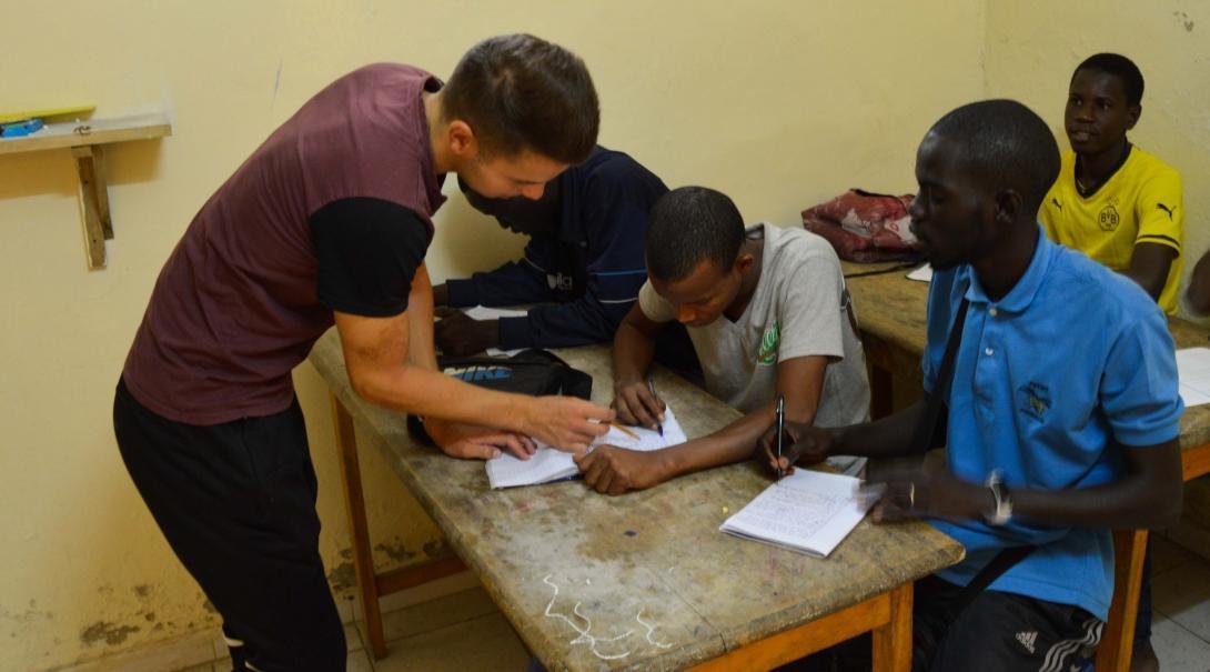 Voluntario trabajando con niños talibé durante su programa de voluntariado para jóvenes en verano.